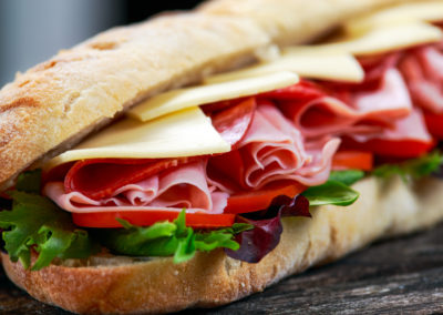 Sandwich With Lettuce, Slices Of Fresh Tomatoes, Salami, Hum And