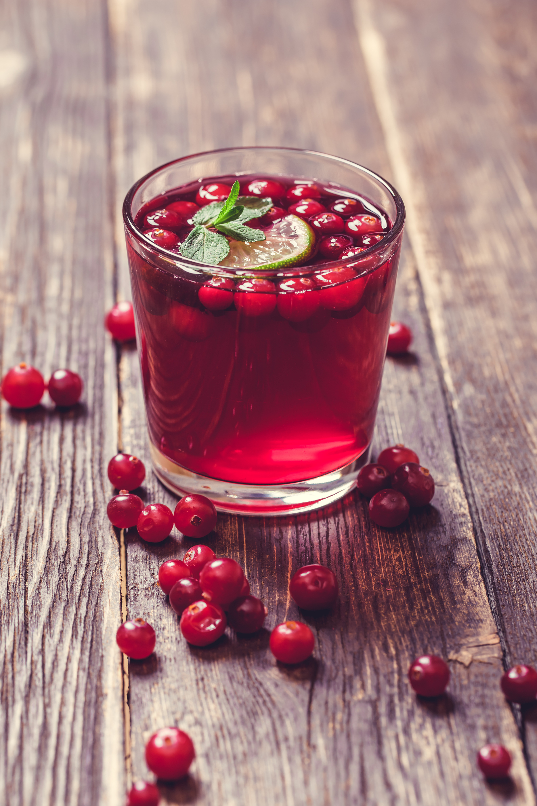Glass of cranberry juice with mint on wooden table